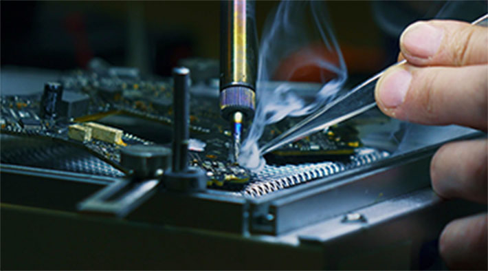 Person soldering a contact on a computer chip