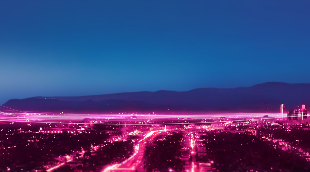 Cityscape with streaks of pink lights on the roads